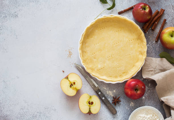 Dough for homemade apple pie in baking tray stock photo