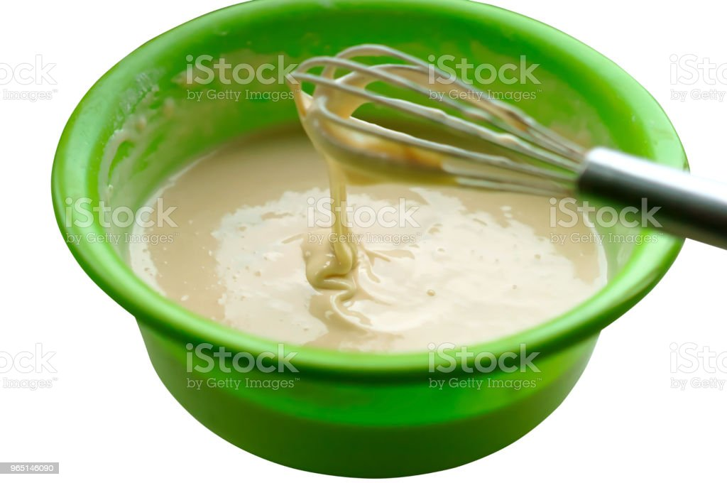 dough in a bowl and whisk for mixing, liquid dough for pancakes, ready dough for baking pancakes royalty-free stock photo