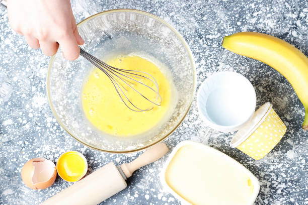 dough in bowl and whisk top view, home baking cooking concept stock photo