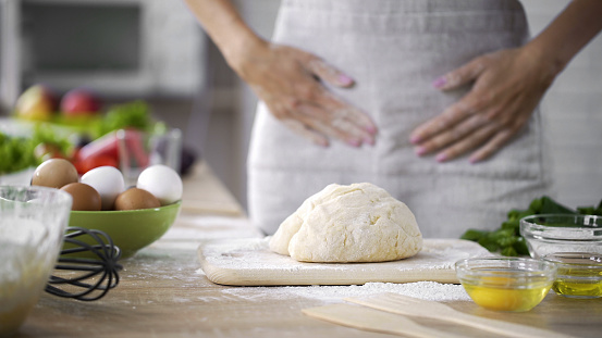 istock Dough on kitchen table with woman in apron standing behind, biscuit cooking 923491682