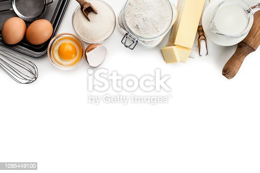 Top view of dough preparation ingredients placed in a row at the top border of a white background making a frame and leaving useful copy space for text and/or logo. Ingredients included in the composition are milk, butter, sugar, eggs and flour. Some kitchen utensils for dough preparation like rolling pin, sieve, baking sheet and wire whisk complete the composition. Predominant color is white. High key DSRL studio photo taken with Canon EOS 5D Mk II and Canon EF 100mm f/2.8L Macro IS USM.