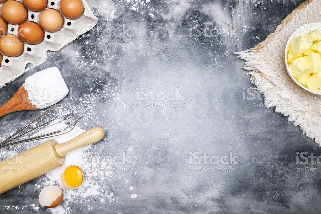 massa de pão receita preparação. Cozer cozinhar de padaria de ingredientes. manteiga de saco, ovo e farinha na placa preta. postura plana na mesa Bare argamassa cimento estilo loft de fundo. Vista superior, copie o espaço. - foto de acervo