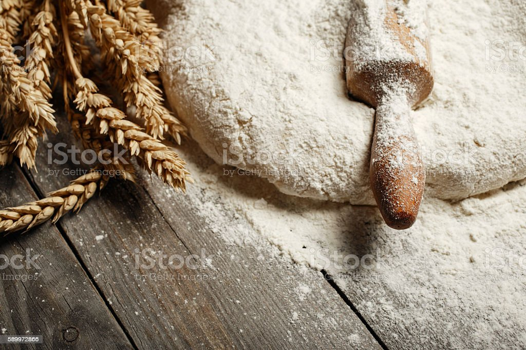 Dough with wooden rolling pin and wheat stock photo