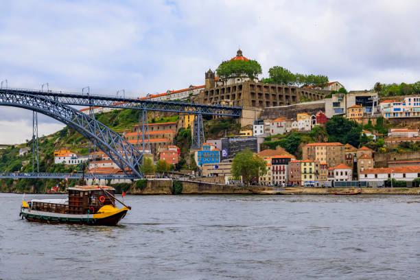 Douro river and Dom Luis I bridge in Vila Nova de Gaia and tourist boats used to transport port wine in Porto, Portugal stock photo
