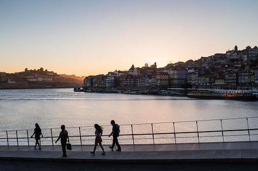 Douro River view, group of people and Ribeira district skyline at dusk, Porto, Portugal.