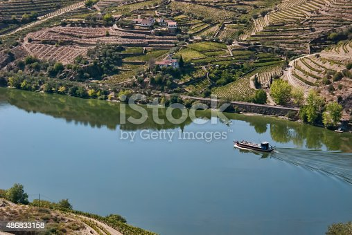 From high atop the southern shore of the Douro River in a vineyard near Tabuaço, Viseu, Portugal, looking across the calm Douro River towards another winery and more vineyards.