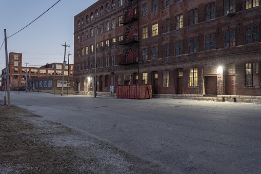 istock Down an industrial street behind a vintage multiple story red brick warehouse with lights 1139534198