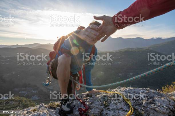 Photo of POV down arm to young man climbing up a rock face