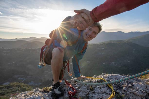 POV down arm to young man climbing up a rock face stock photo