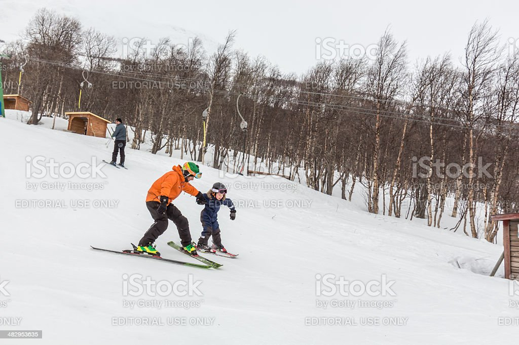 Down hill skiing with help from the teacher stock photo