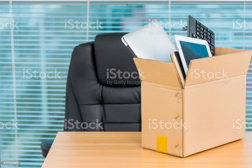 Down sizing concept Cardboard box filled with office supplies. 2015 Stock Photo