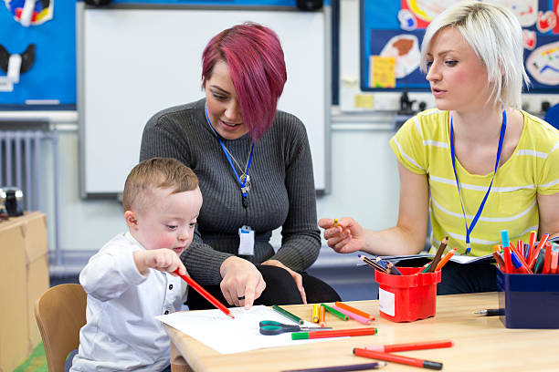 down syndrome boy at nursery - preschool teacher stock pictures, royalty-free photos & images