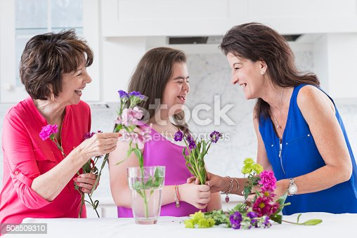 623358818 istock photo Down syndrome girl, mother, grandma arranging flowers 508509310