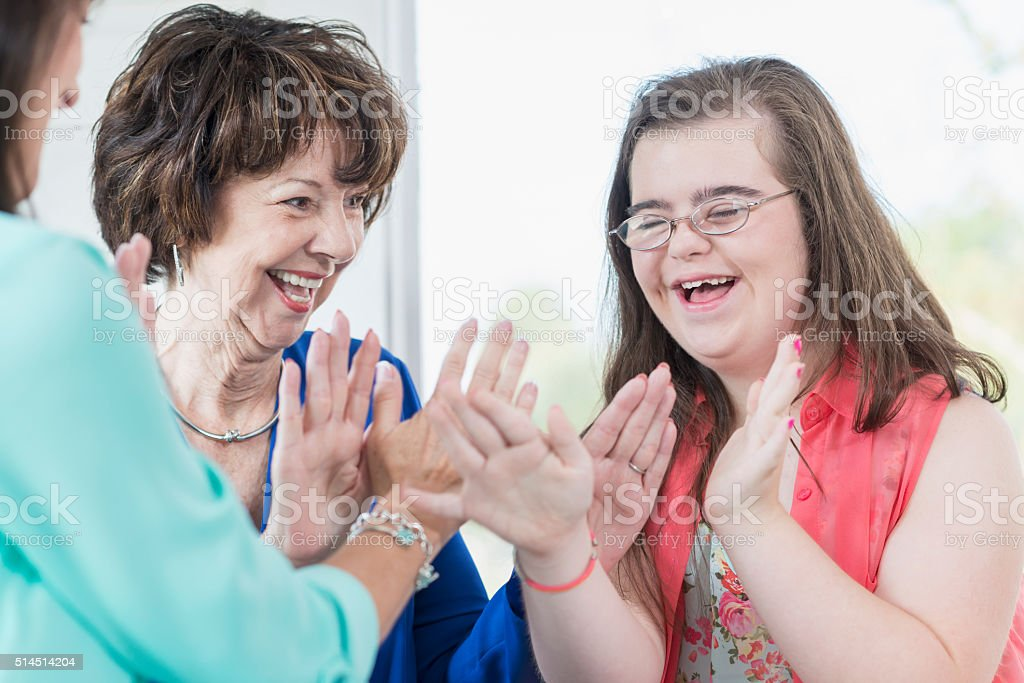 Down syndrome girl with family playing games stock photo