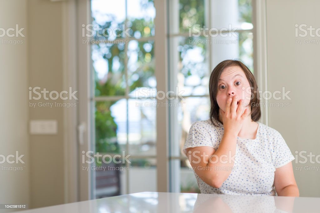 Down syndrome woman at home cover mouth with hand shocked with shame...