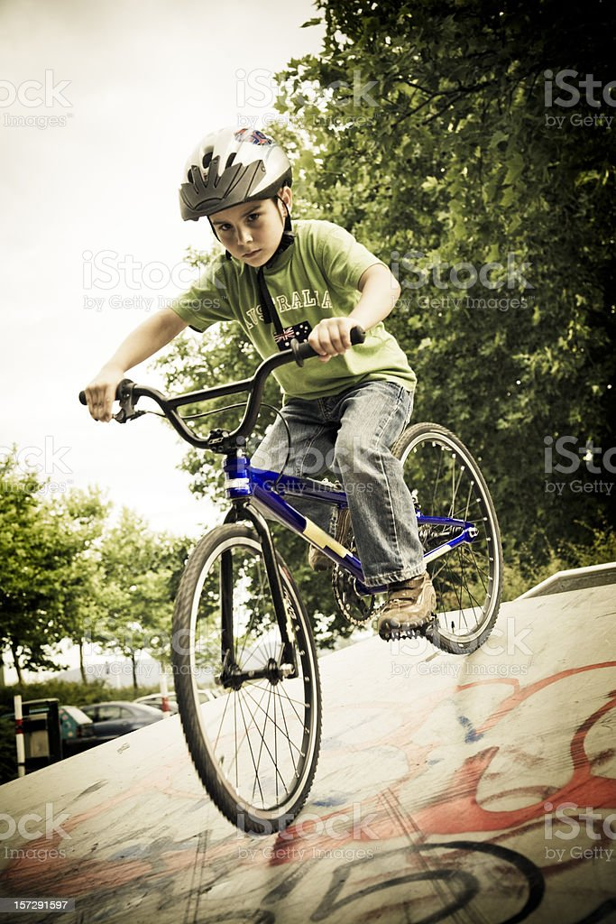 young boy speeding down the halfpipe with his bmx bike, action sports...