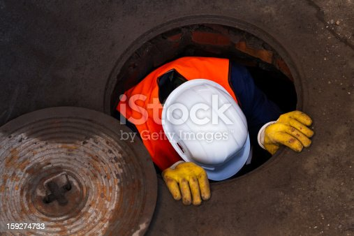 A Worker, man going down to work in sewage.