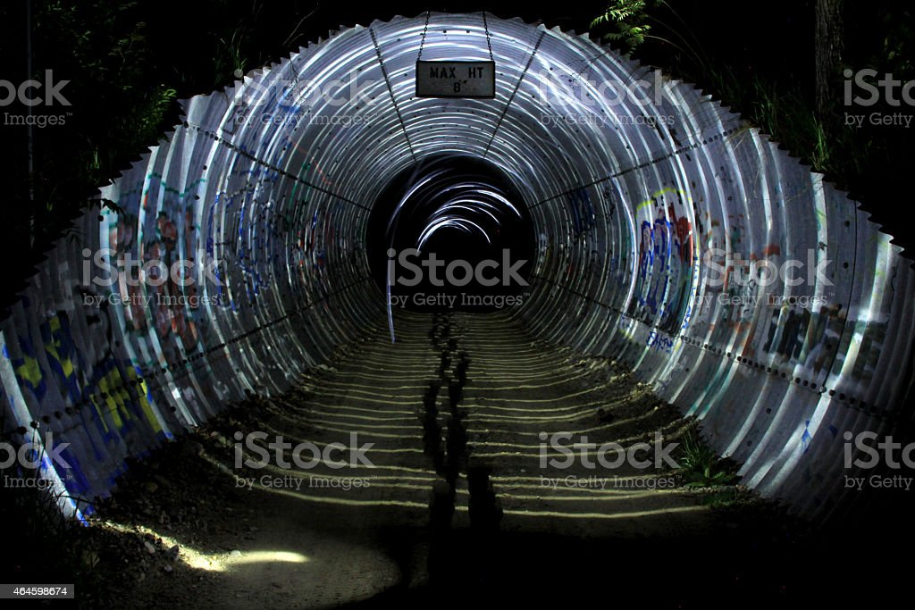 Long exposure of walking through a highway underpass at night while...