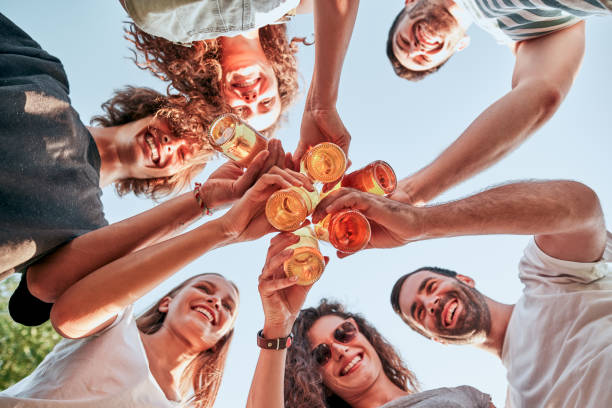 Down view image of a group of happy friends clinking beer bottles standing together stock photo
