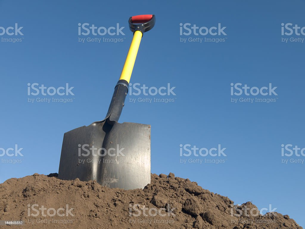 Down view of a shovel in a pile of soil stock photo