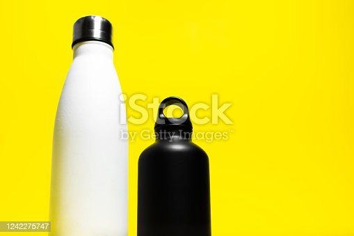 1129148925 istock photo Down view of two half reusable eco, steel and aluminum, thermo water bottle, white and black color, isolated on yellow background. 1242275747