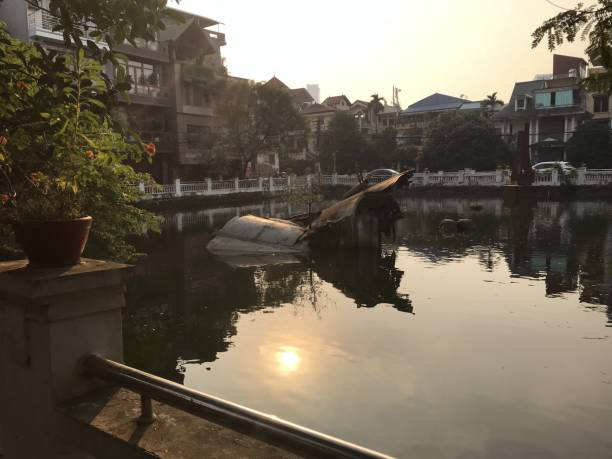 Downed US B52 Bomber at rest in a residential area In Han Noi, Vietnam the sun reflects on the still water and a downed US 52 Bomber aircraft that today still lays to rest in a small pond in a residential area in Hanoi. viet cong stock pictures, royalty-free photos & images