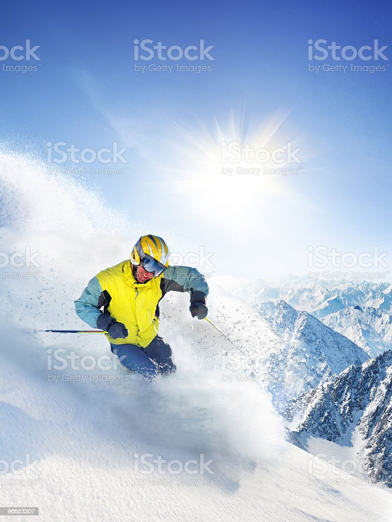 Downhill male skier spraying snow as he glides down mountain stock photo