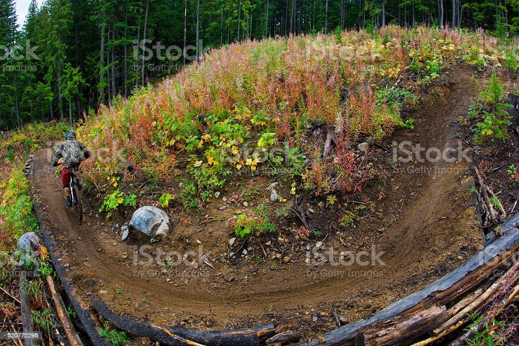 A male downhill mountain biker rides through a corner on a steep...