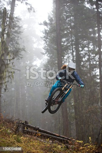 A woman rides her downhill mountain bike off a jump on a trail in British Columbia, Canada on a rainy and foggy day. She is wearing a full face helmet and rides a modern downhill mountain bike.
