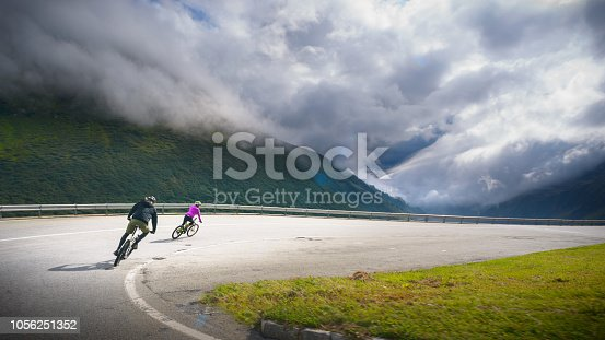 Young active couple mountain biking downhill on mountain road - Grimselpass, Swiss Alps, Switzerland.