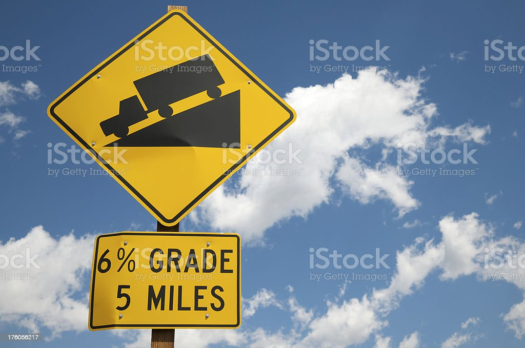 Downhill Sign Against Blue Sky stock photo