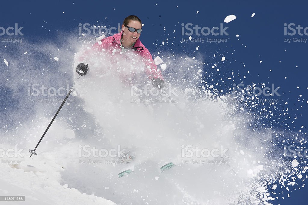 Downhill Skier Throwing Snow Against Blue Sky royalty-free stock photo