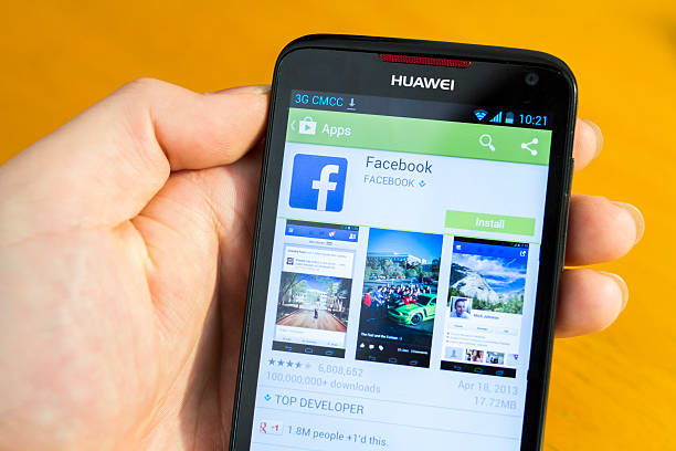 Download Facebook App from Google Play Shanghai, China - May 4, 2013: Man using  a Huawei Ascend D1 Quad XL cellphone to download Facebook app from Google Play. Huawei, originated in China, is now a leading global ICT solutions provider. Google Play is an mobile app store powered by Google, an American multinational corporation that provides Internet-related products and services, including internet search, cloud computing, software and advertising technologies. Facebook is the world's most popular social networking website, and offers mobile services.  huawei stock pictures, royalty-free photos & images