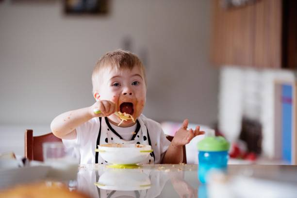 down's syndrome sweet boy eating spaghetti - manonallard stock photos and pictures