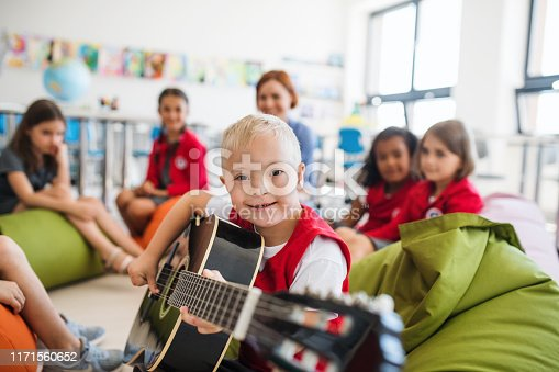 A down-syndrome boy with school kids and teacher sitting on the floor in class, playing guitar.