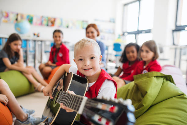 un garçon de down-syndrome avec des gosses d'école et le professeur s'asseyant dans la classe, jouant la guitare. - handicap photos et images de collection