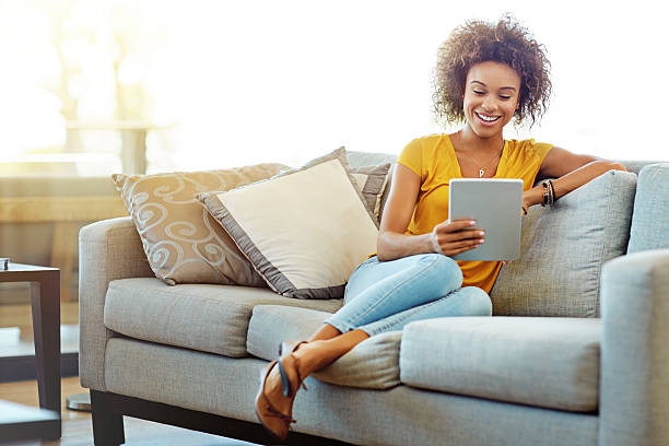 Downtime in the digital age Shot of a young woman using a digital tablet on a relaxing day at home touchpad stock pictures, royalty-free photos & images