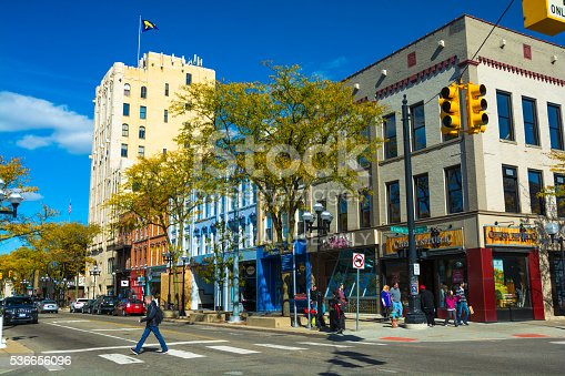 Ann Arbor, United States - October 18, 2015: Pedestrians walking on and crossing Main street in Downtown Ann Arbor, with the historic First National Bank building at the end of the block.