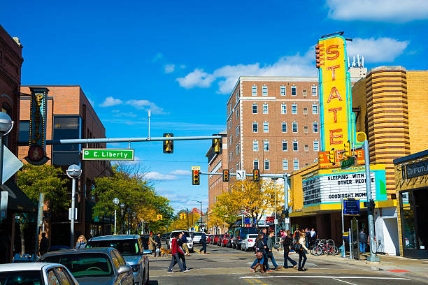 Downtown Ann Arbor with the State Theater and pedestrians Ann Arbor, United States - October 18, 2015: Pedestrians crossing State Street in Downtown Ann Arbor, Michigan with State Theater on the right.  Picture taken in Autumn. ann arbor stock pictures, royalty-free photos & images