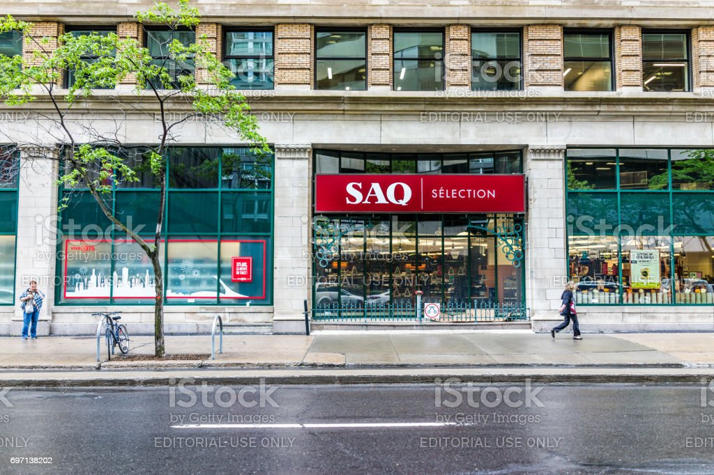 Downtown area of city in Quebec region with SAQ store and red sign on street during wet rain on cloudy day and people walking stock photo