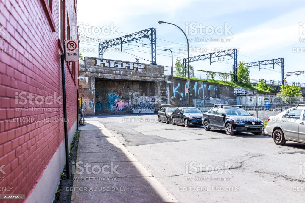 Downtown area with street parking signs, cars and graffiti during day outside in Quebec region city stock photo