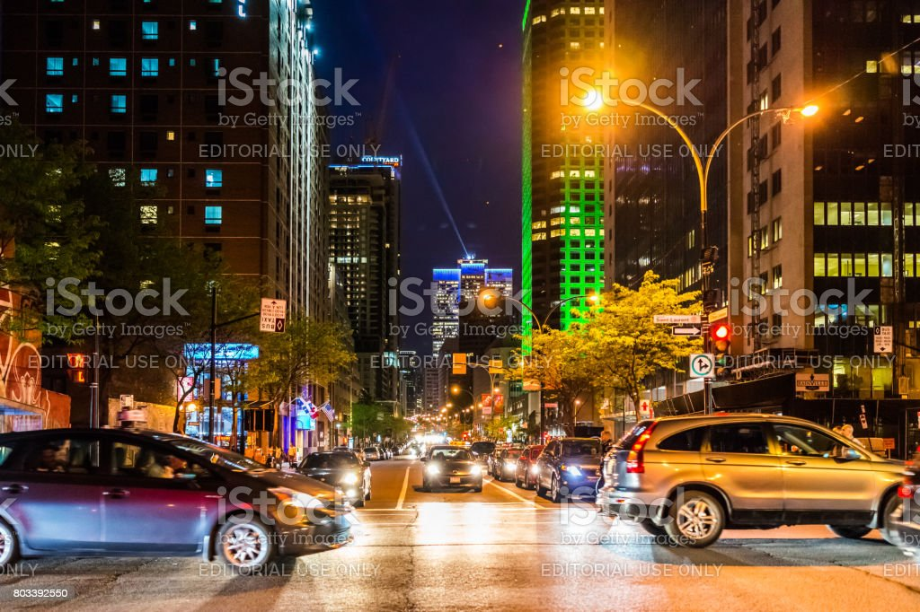 Downtown area with traffic cars and Complexe Desjardins green building at dark night evening outside in Quebec region city stock photo