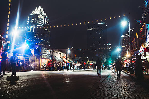 Downtown Austin at Night on Sixth Ave Weekends finds Austin, Texas 6th Avenue closed to cars, allowing foot traffic to easily come and go from the city nightlife, bars, and clubs.  Horizontal, long exposure image. nightlife stock pictures, royalty-free photos & images