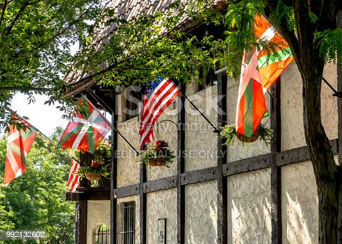 Basque and American flags waving on a historic building