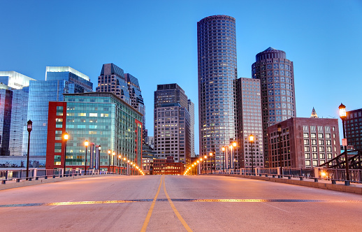 City street leading into downtown Boston at dusk. Boston is the largest city in New England, the capital of the state of Massachusetts. Boston is known for its central role in American history,world-class educational institutions, cultural facilities, and champion sports franchises.