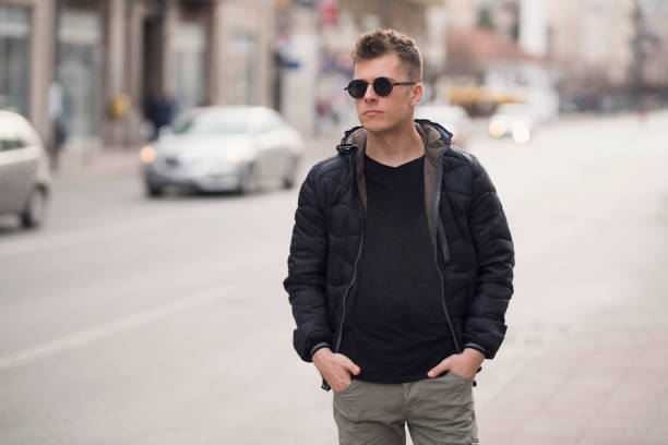 Downtown Boy Fashion portrait of a young man walking down the city streets. mens fashion stock pictures, royalty-free photos & images