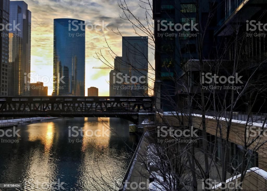 Downtown Chicago as evening sets and reflects cityscape onto Chicago River during winter. stock photo