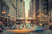 Chicago, United States- August 22, 2015:  Blurred motion of the traffic downtown Chicago.   We see the blur of the motion of the aerial train-metro in the background and cars in the foreground , while other vehicles are stop at traffic lights in downtown Chicago.