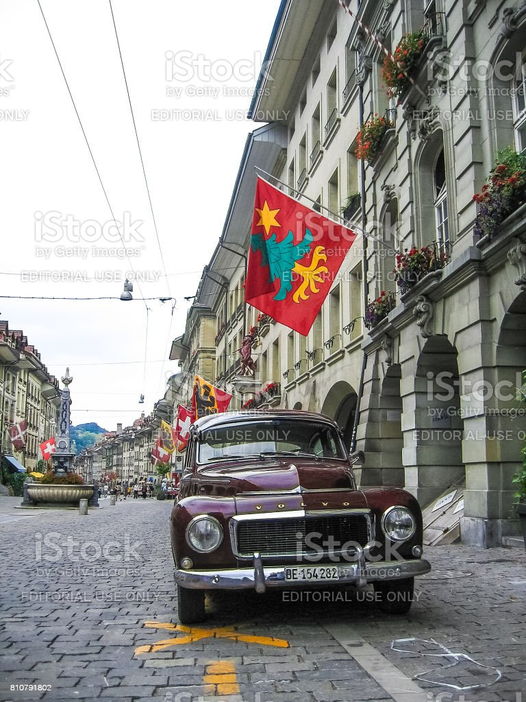 Downtown city during summer with old vintage Volvo car, flower decorations and flags stock photo
