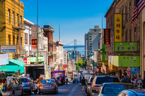 centrum stadsleven in een drukke straat van chinatown san francisco. bekijken met vele mensen, winkels en auto - uitkijk naar de oakland bay bridge. - chinatown stockfoto's en -beelden